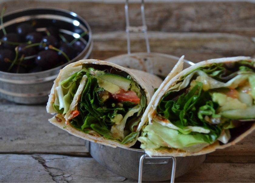 Wraps mit Salat, Gurke, Avocado, Tomaten, Paprika-Aufstrich und frischen Kräutern - dazu Kirschen als Nachtisch